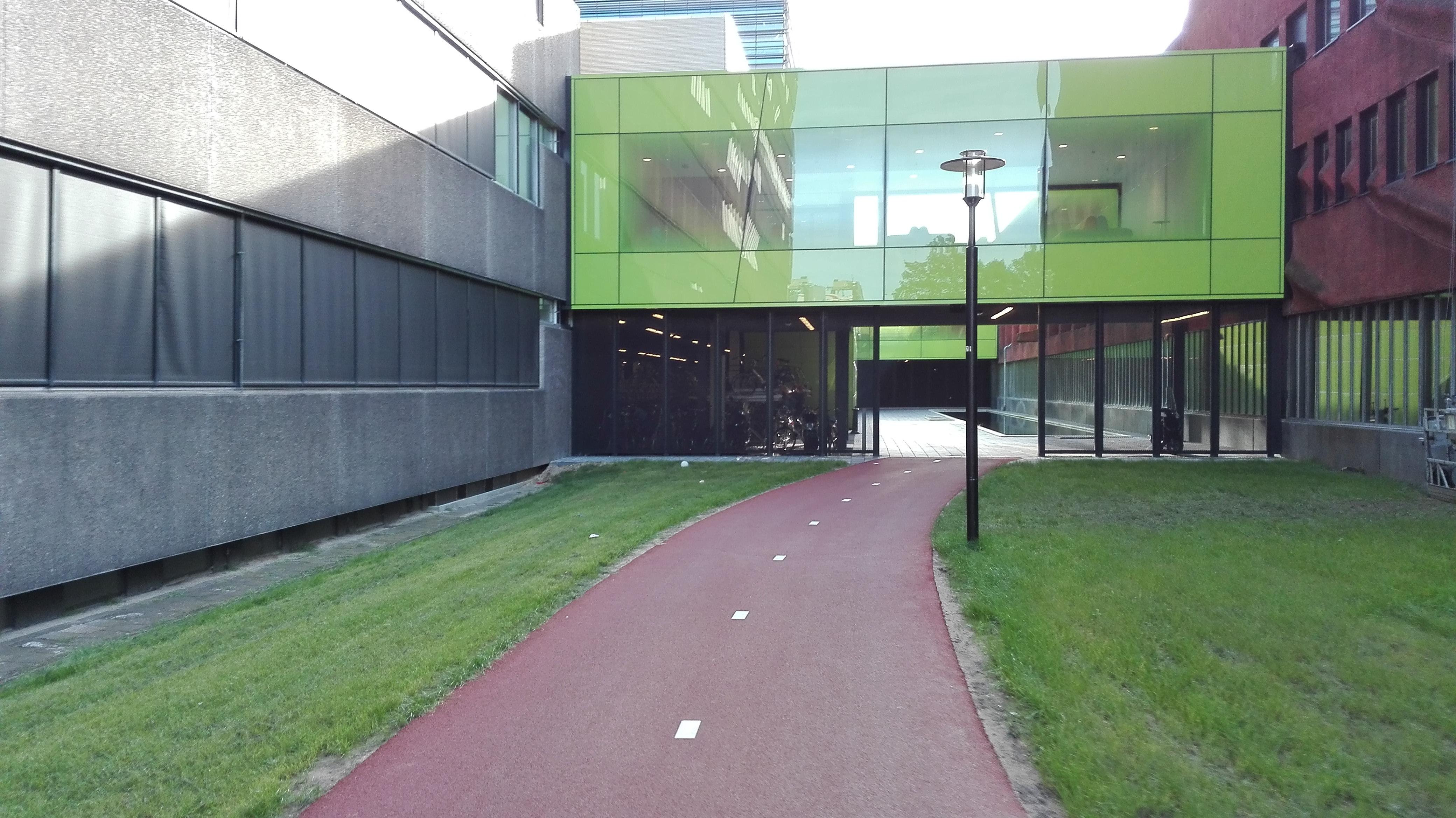 Szeroka droga rowerowa prowadząca do parkingów